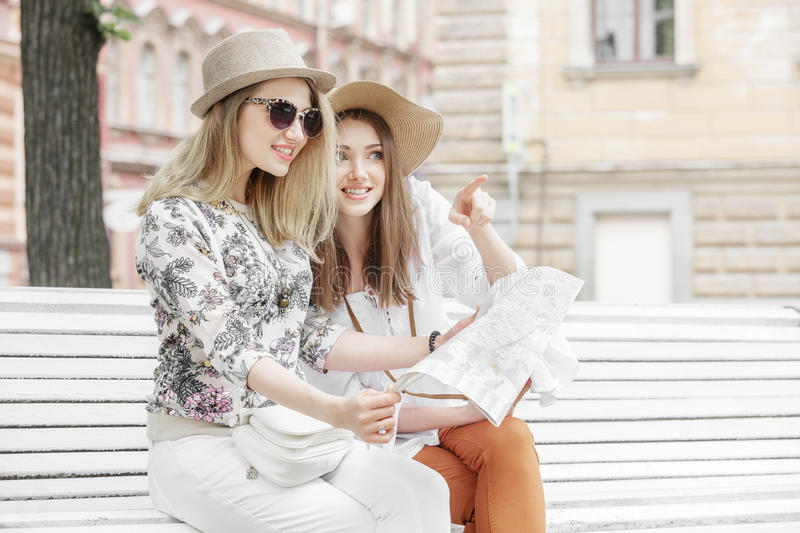 Beautiful girls tourists are looking for an address on the map sitting on the bench. They are wearing hats and smiling. Outdoors stock image