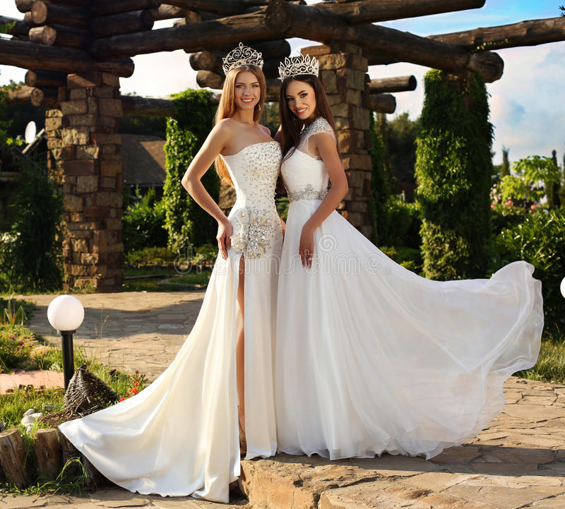 Beautiful girls wearing elegant dresses and luxurious crown. Fashion outdoor photo of beautiful girls with long straight hair wearing elegant dresses and royalty free stock images