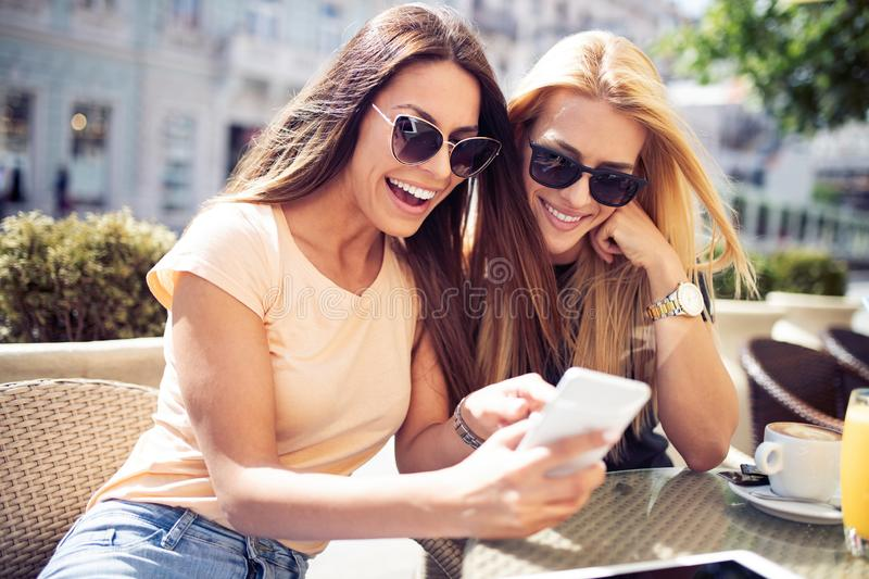Beautiful girls having fun smiling together in a cafe outdoor royalty free stock photography