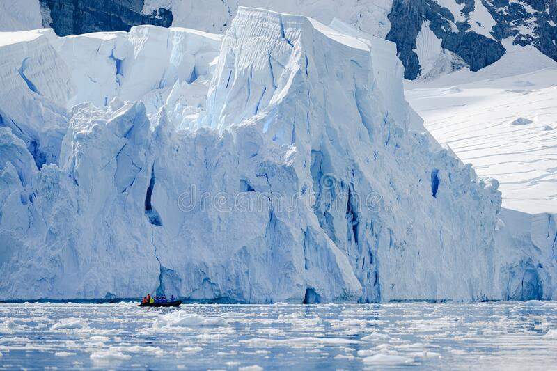 Glacier wall in Antarctica, majestic blue and white ice wall with Zodiac in front. royalty free stock photos