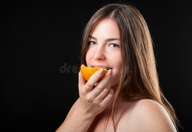 Beautiful glad woman and fresh juicy orange royalty free stock image
