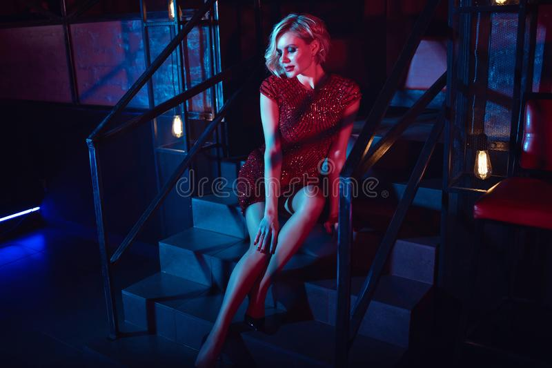 Beautiful glam blond woman with provocative make up wearing red short fitted sequin dress sitting on the stairs in the night club stock photography
