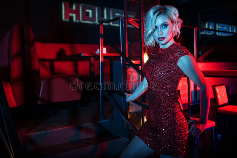 Beautiful glam blond woman standing on the stairs in the night club in colourful neon lights stock photography