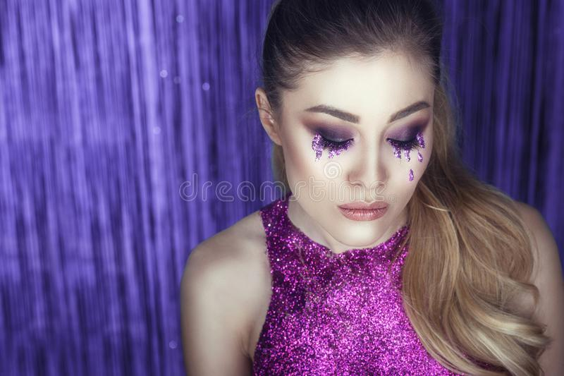 Beautiful glam model with artistic make up, glitter tears, wavy ponytail and top made of purple glitter posing against the tinsel royalty free stock photography
