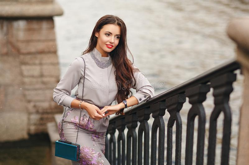 A beautiful, glamorous and stylish brunette girl stands on a bridge in the city and smiles. Street Style stock photos