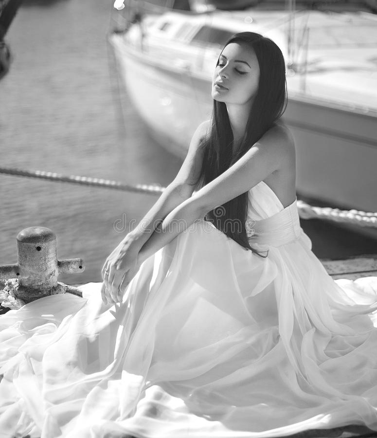 Beautiful, glamorous woman, girl sitting at pier in yacht club n. Ear sail boats. Fashion, magazine picture stock photos