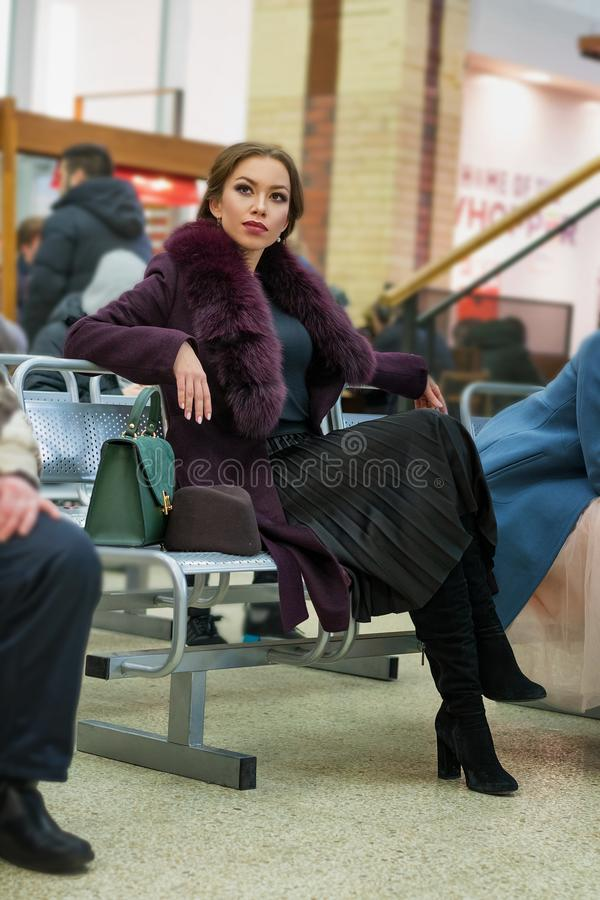Beautiful glamorous woman with a make-up in a Burgundy coat sitting at the station royalty free stock photos