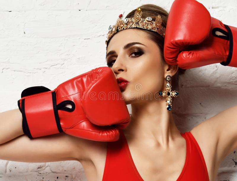 Beautiful glamour woman with red Boxing Gloves and fashion gold crown and earrings on brick wall stock images
