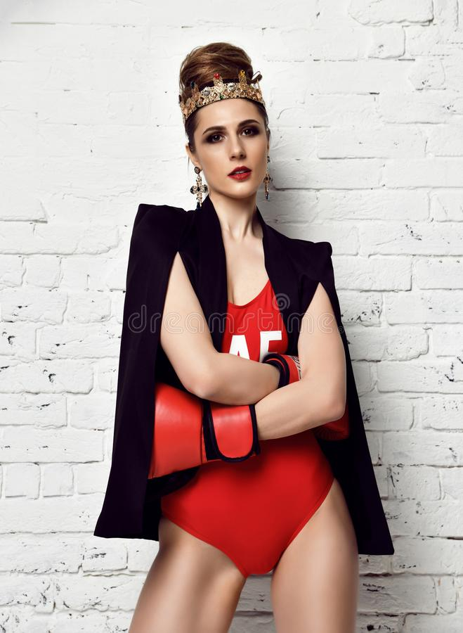 Beautiful glamour woman with red Boxing Gloves and fashion gold crown and earrings on brick wall royalty free stock photography