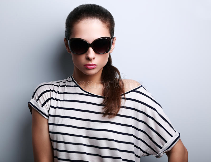 Beautiful glamour woman posing in fashion sunglasses on blue background royalty free stock photos