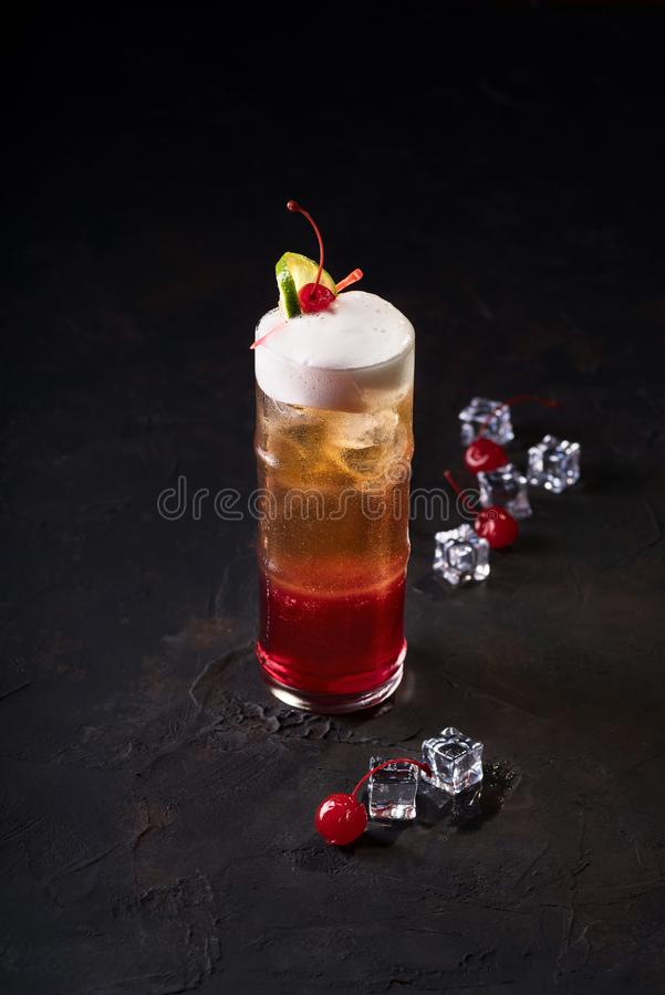 Beautiful glass with facets. Filled with a refreshing drink. Alcoholic cocktail on a black background. royalty free stock images
