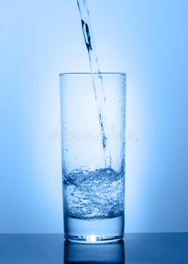 Beautiful glass with water on a blue background stock photo
