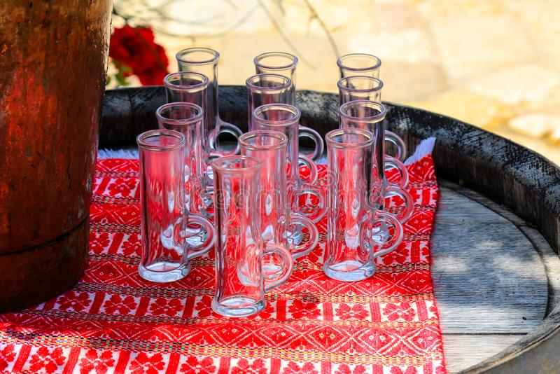 Beautiful glasses stand on a textile ethical red background and an old wooden barrel outdoors. Glass for strong alcohol royalty free stock images