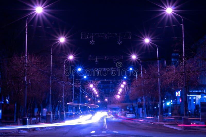 Beautiful glow of night lights along the road. Concept of synthwave. Beautiful glow of night lights along the road where cars fly by. Concept of synthwave royalty free stock photo