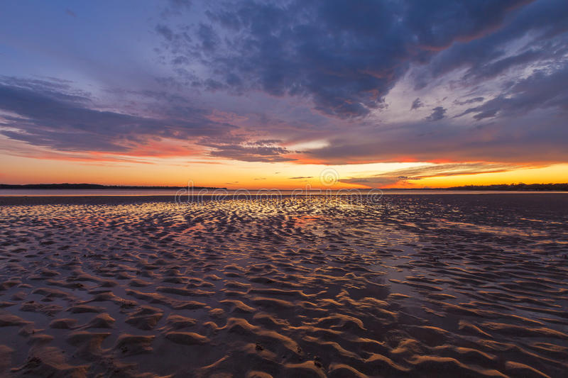 Beautiful glowing sunset reflections in sand ripples, Inverloch, Australia royalty free stock images