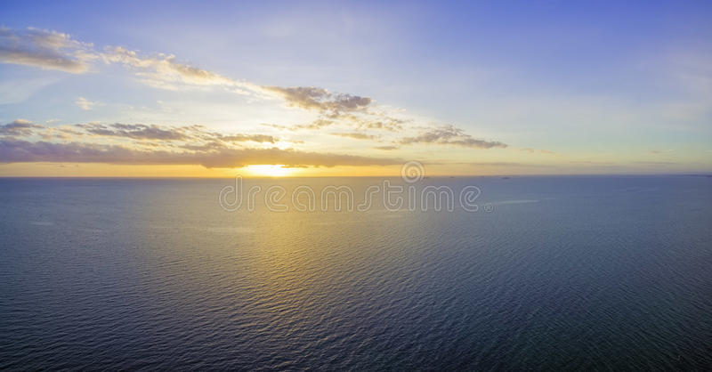 Beautiful glowing yellow-purple sunset. Over ocean waters with tiny ships in the distance stock photography