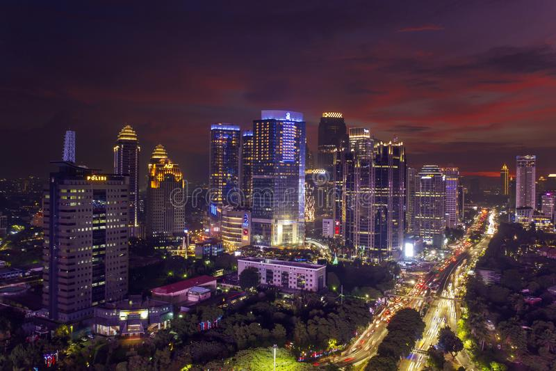 Beautiful glows skyscraper with heavy traffic. JAKARTA - Indonesia. January 02, 2019: Beautiful aerial view of glowing skyscrapers with heavy traffic at evening stock images