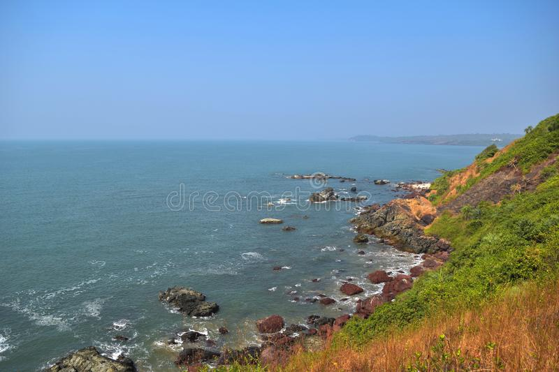 Beautiful Goa beach, rocky coast and blue sea view from high green cliff, India at the clear sky background stock image