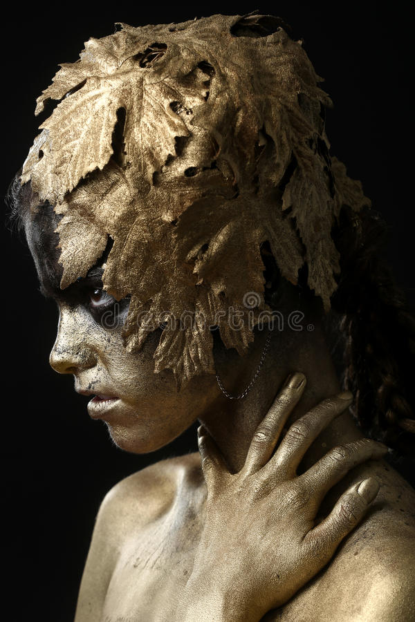 Beautiful Gold Painted Woman in Conceptual Beauty Themed Image stock photo