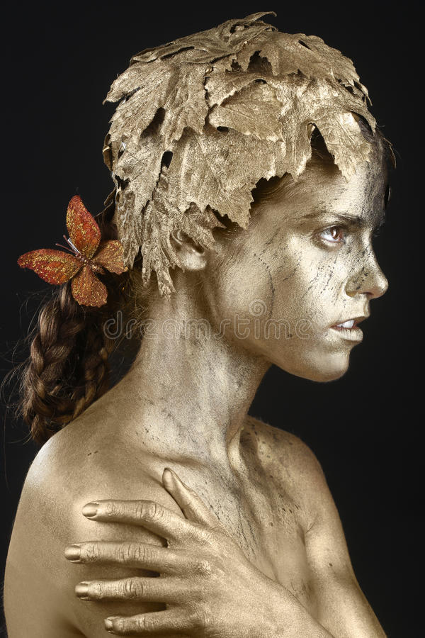 Beautiful Gold Painted Woman in Conceptual Beauty Themed Image royalty free stock image