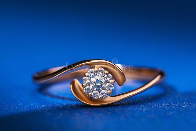 Beautiful gold ring with precious stones on a blue background royalty free stock photos