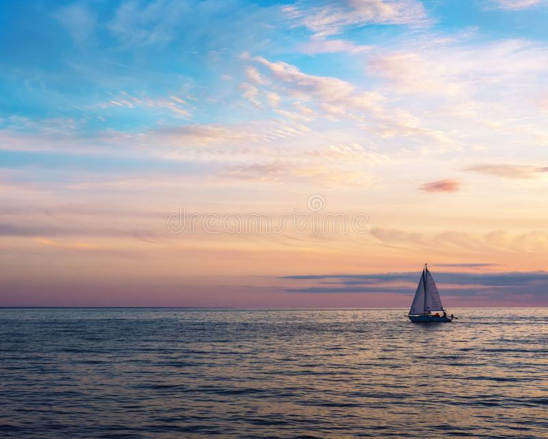 Beautiful gold sunset with a sailboat sailing. Air clouds of different colors stock photos