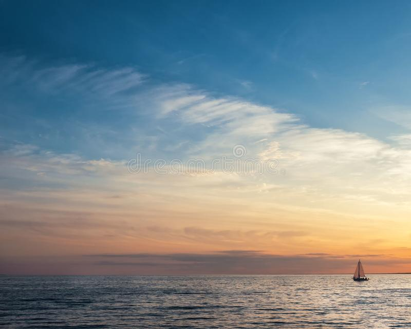 Beautiful gold sunset with a sailboat sailing. royalty free stock photo