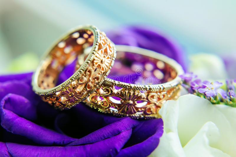 Beautiful gold wedding rings with patterns, close-up. Two gold rings, blurred background with white and blue flowers stock image