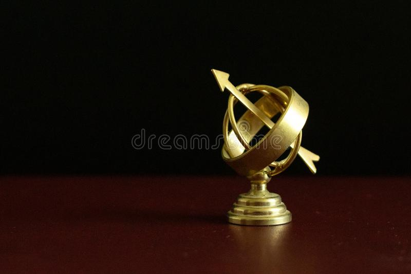 Beautiful golden antique astrolabe globe in darkness stock photography