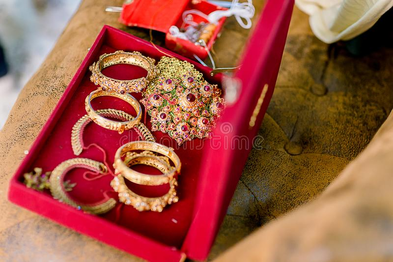 Beautiful golden bracelets and rings on bed. Wedding gold bangles and bracelets. Colorful and gold bridal wedding bangles royalty free stock photography