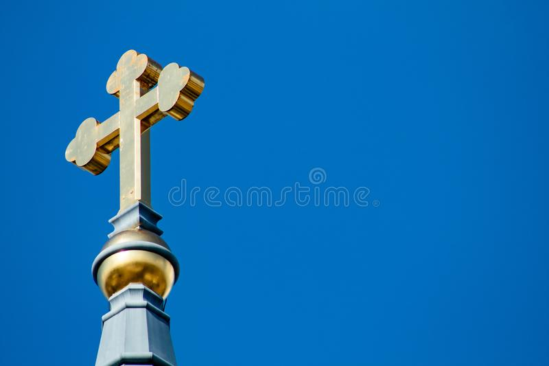 Golden Cross in the Sky. Beautiful golden cross with a cloudless sky back drop stock image