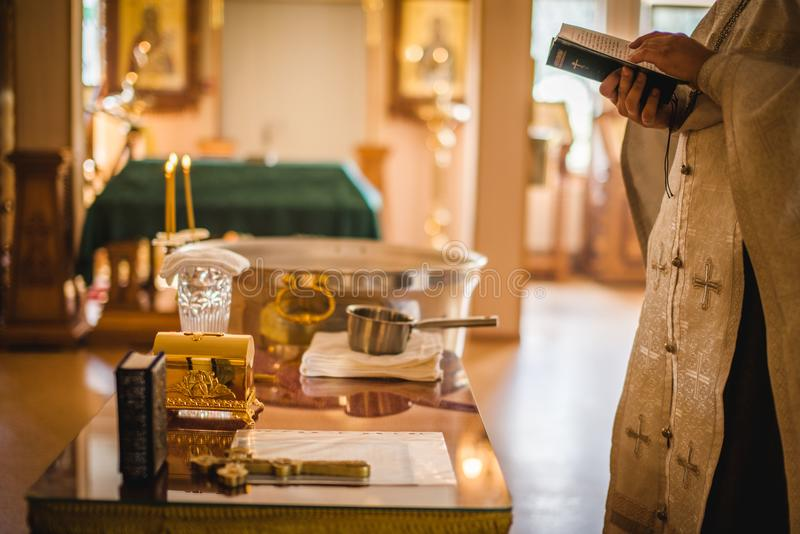 Beautiful golden cross in male hands of priest wearing gold robe on ceremony in christian cathedral church, holy sacramental event. Priest Holding A Bible stock image