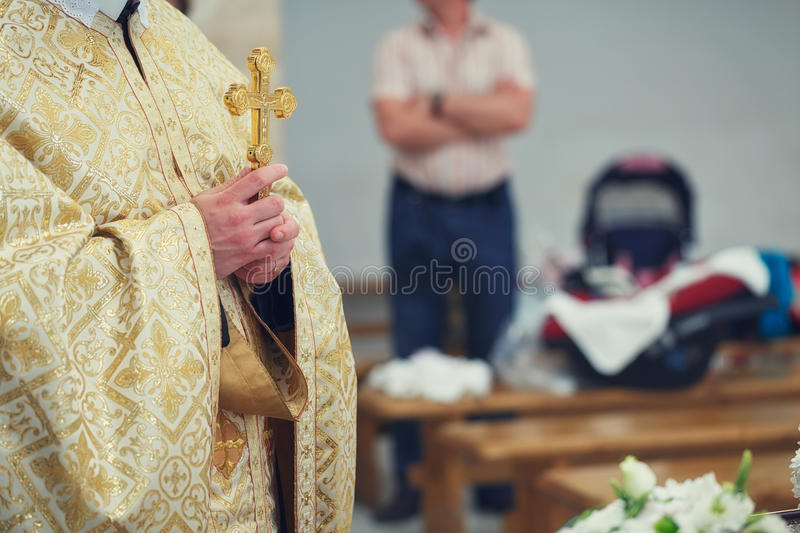 Beautiful golden cross in male hands of priest. Wearing gold robe on ceremony in christian cathedral church, holy sacramental event stock photography
