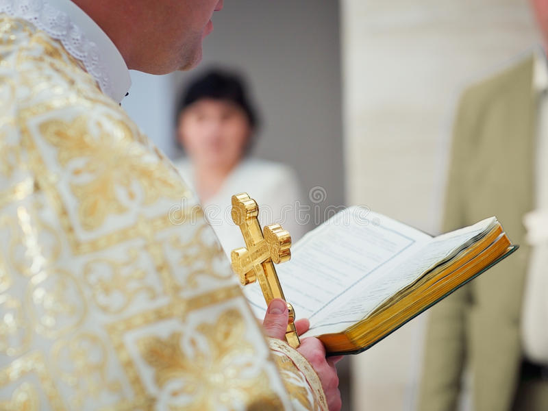 Beautiful golden cross in male hands of priest. Wearing gold robe on ceremony in christian cathedral church, holy sacramental event. Priest Holding A Bible royalty free stock photo