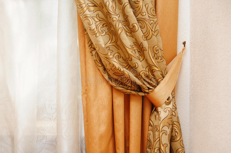 Beautiful golden curtain in the bedroom. Near window stock image