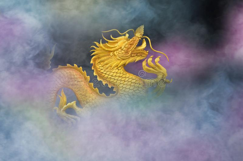 Beautiful golden dragon in colored smoke royalty free stock photo