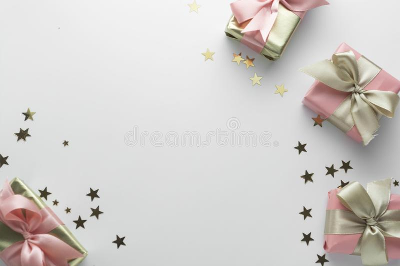 Beautiful golden gifts glitter conffeti pink bows ribbon on white. Christmas, party, birthday background. Celebrate shinny stock image