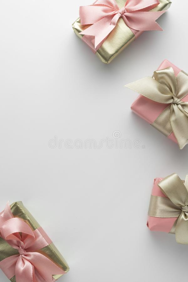 Beautiful golden gifts with pink bows ribbon on white. Christmas, party, birthday background. Celebrate shinny surprise boxes copy royalty free stock image