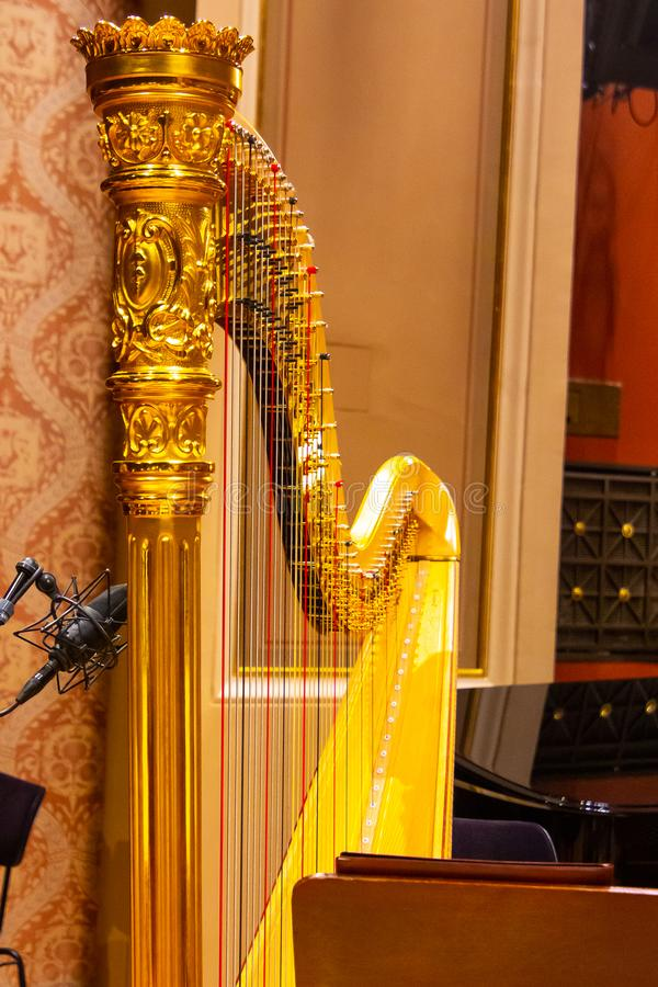 Beautiful golden harp strings close up. Musical instruments of the Orchestra in philharmonia stock photography