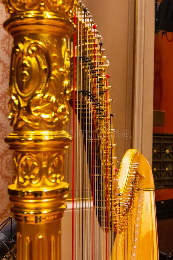 Beautiful golden harp strings close up. Musical instruments of the Orchestra in philharmonia royalty free stock photos