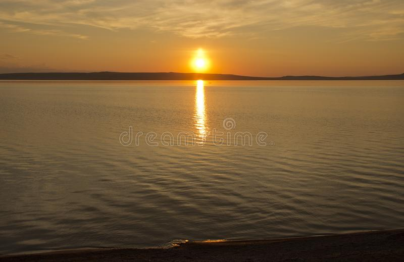Beautiful golden orange sunset over the lake. The sun sets turning the sky yellow, orange & red tones & reflects in the lake.  royalty free stock photo