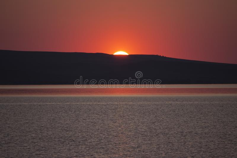 Beautiful golden orange sunset over the lake. The sun sets turning the sky yellow, orange & red tones & reflects in the lake.  stock image