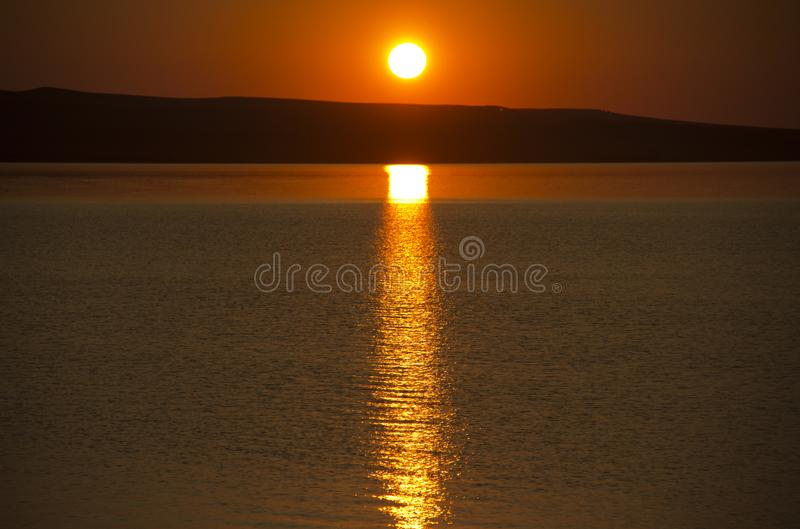 Beautiful golden orange sunset over the lake. The sun sets turning the sky yellow, orange & red tones & reflects in the lake.  stock photography