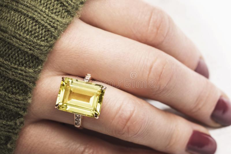 Beautiful golden ring with yellow sapphire and small cubic zirconias on a womans hand. Close-up stock photo