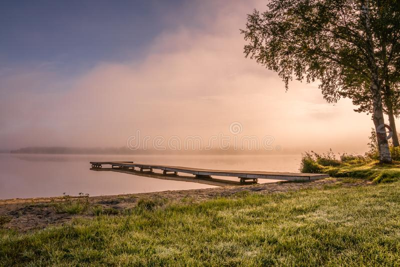 Beautiful golden Sun glows through fog at lake during early sunrise, long wooden bridge, trees, sky reflection in calm water. Northern Sweden, outside of Umea stock images