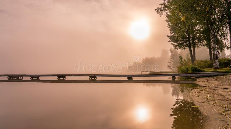 Beautiful golden Sun glows through fog at lake during early sunrise, long wooden bridge, trees, sky reflection in calm water. Northern Sweden, outside of Umea stock photos