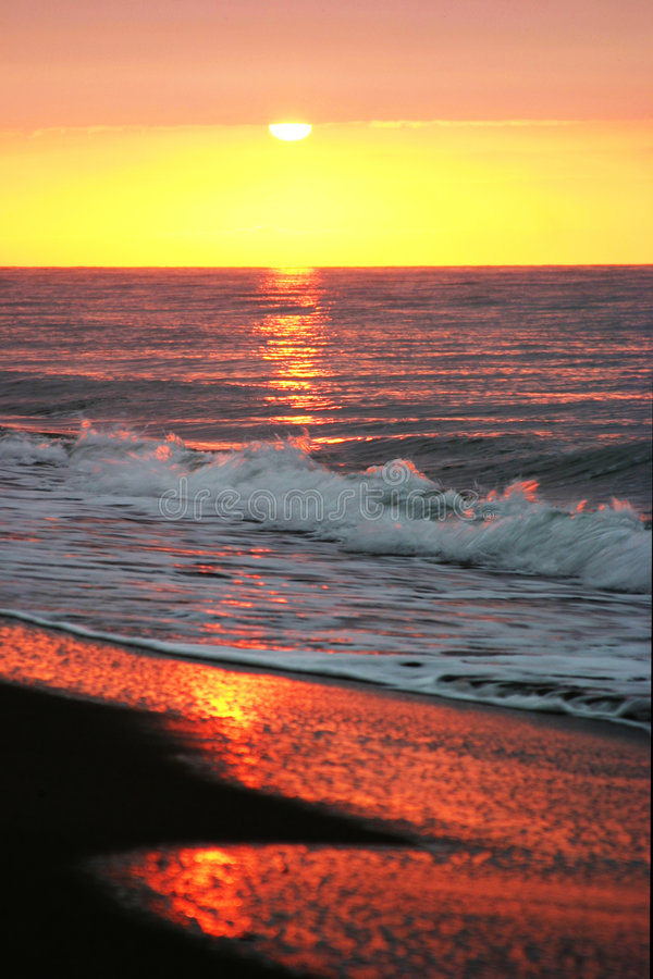 Beautiful golden sunrise as seen from the sandy beach in Marbella. Beautiful, glorious golden sunrise to start the day the Marbella way. Waves gently lap onto stock photo