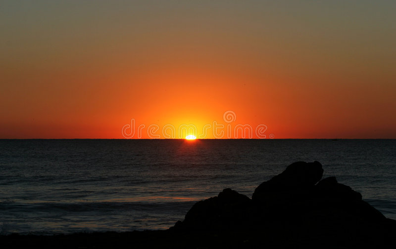 Beautiful golden sunrise in southern Spain as seen from the beach. A Golden sunrise to start the day in Spain as seen from the beach, past some rocks and over royalty free stock photo