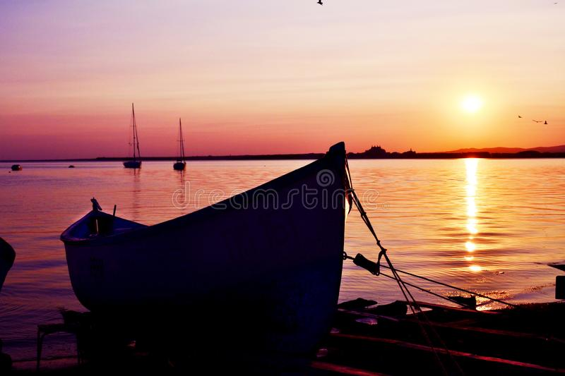 Beautiful Golden Sunset on the Lake with Fish Boat royalty free stock photo