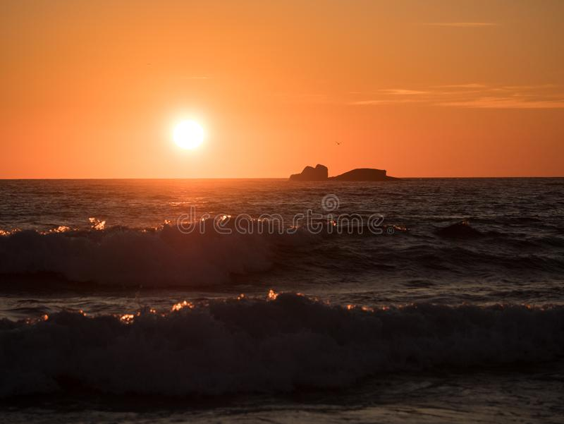 Beautiful golden sunset on ocean with waves in foreground stock image